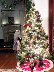 A mouse performer contemplates the Christmas tree before