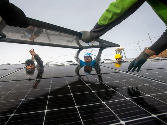 Gwendolyn Tsosie helps install solar panels on Wednesday at the Ojo Encino Chapter house.