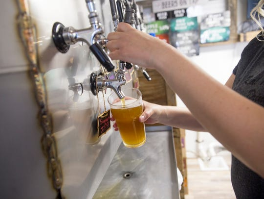 In Aztec, 550 Brewing Manager Kara Paschall pours a beer Thursday. Thanks to a state law, the brewery can now do the same thing on Sundays as well.