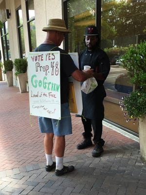 A man (left) is seen in downtown Jackson wearing a sign supporting Initiative 48, which would have legalized marijuana in Mississippi.