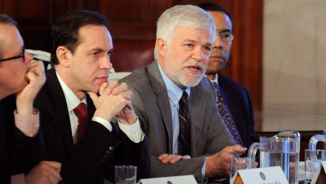 In this Dec. 17, 2014 file photo, New York environmental conservation commissioner Joseph Martens, right, explains the department's findings on hydraulic fracturing during a cabinet meeting at the Capitol in Albany. At left is acting health commissioner Dr. Howard Zucker.