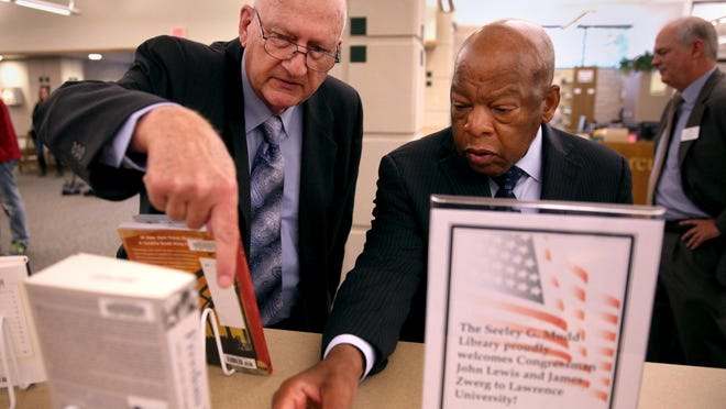 James Zwerg (left) and U.S. Rep. John Lewis look through some of the books on display about the civil rights movement at the Seeley G. Mudd Library before Lawrence University's commencement Sunday in Appleton. Lewis gave the commencement address.