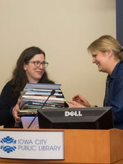 Mindwell Egeland, left, director of the Patients' Library at the University of Iowa's Children's Hospital, accepts books from around the world handed to her by Kristin Vidarsdottir, director of the Reykjavik UNESCO City of Literature, at the Iowa City Public Library on April 5, 2018. Photo by Desirae Blake.