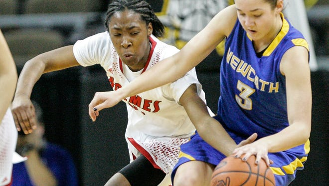 Holmes' Jynea Harris tries for a steal against NewCath's Ansley Davenport during the first quarter of their semifinal game in the Girls' Ninth Region Basketball Tournament at NKU Saturday, March 7, 2015.
