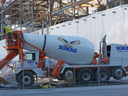 Concrete is poured from a Sonag Ready Mix truck in February 2017, at the site of the new Milwaukee Bucks arena. Sonag was among companies under federal investigation for breaking rules giving contracts to minority run businesses.