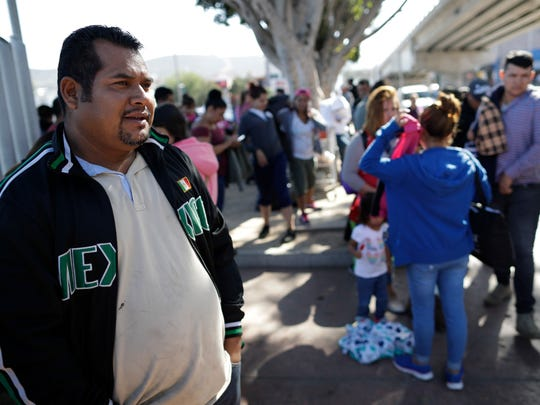 In this Wednesday photo, Jose Osmin Aparicio, left, waits with others to request political asylum in the United States, across the border in Tijuana, Mexico. Aparicio's life was made so miserable by the MS-13 gang in his native El Salvador that he had no choice but to flee in the dead of night with his wife and four children, paying a smuggler $8,000 to get to the border and take their chances with the American asylum system.
