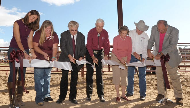 NMSU president Garrey Carruthers, center, is joined by Senator Mary Kay Papen, third from left, College of Agricultural, Consumer and Environmental Sciences (ACES) interim dean Jim Libbin, far right, and various other campus and community leaders on Friday during a special ribbon-cutting event at the site of the new therapeutic riding arena located on campus adjacent to the equestrian center.