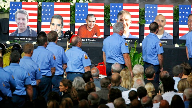 Firefighters from Prescott, Ariz., walk past photos of the fallen firefighters during a memorial service at Tim's Toyota Center in Prescott Valley, Ariz., on Tuesday, July 9, 2013. Nineteen Granite Mountain hotshot firefighters were killed June 30, 2013, battling the Yarnell Hill Fire outside Yarnell, Ariz. An investigation into the cause of their deaths is painful but necessary, experts say.