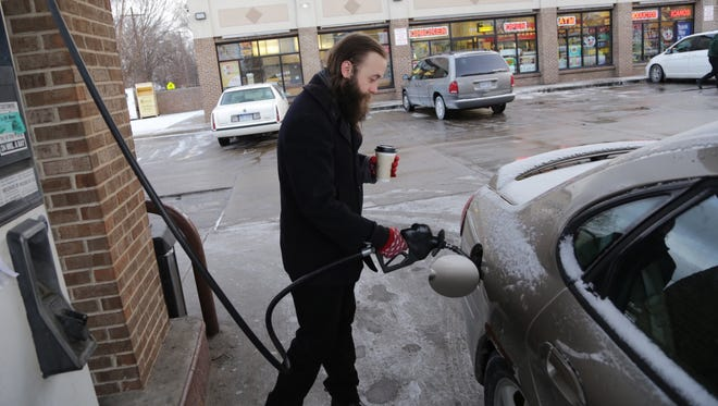 Jackson Gregory of Detroit pumps gas at the Citgo station at the corner of W. Vernor Hwy. and Clark Street in Detroit's South side on Monday, Jan. 5, 2015.