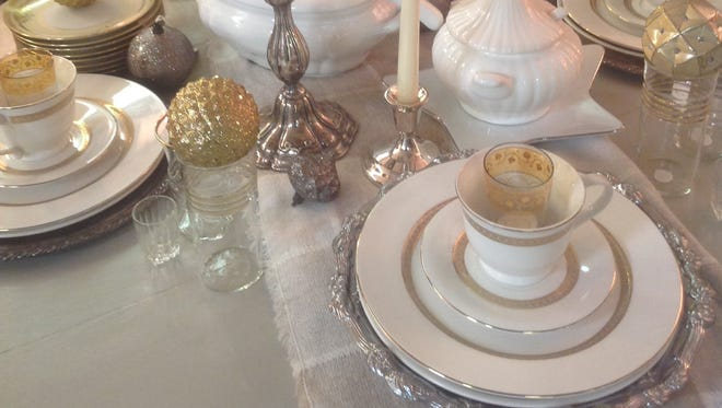 Ruth McGrath, of Salvage Sisters, styles a table for the holidays using a mix of golds, silvers and coppers. McGrath specializes in mixing and matching dishes and patterns to create a table filled with interest and glam.