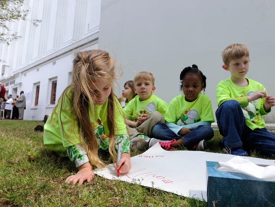 Pre-K students write their names on posters before