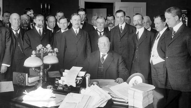 President William Howard Taft (seated) signs the Arizona Statehood Bill in Washington, D.C., on the morning of Feb. 14, 1912.