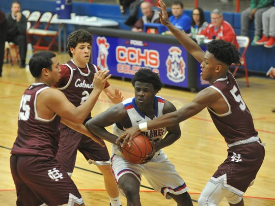 Henderson County defenders, from left, Jadal Fletcher, Corey Stewart and Isaac Anglin surround Christian County's Detorrion Ware in the second half of Saturday's game at Christian County High School in Hopkinsville.
