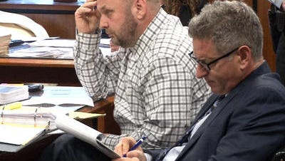 Alan Bienkowski, wearing a plaid shirt, is seated next to his attorney, Michael Schreiber, at his trial for the murder of Anthony Verdicchio.