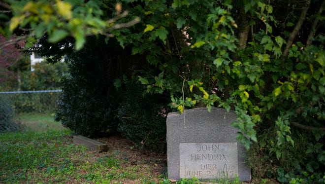 John Hendrix's gravestone sits under shrubs in Oak Ridge's Hendrix Creek subdivision Wednesday, Oct. 25, 2017.
