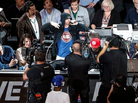 Eminem cheers the crowd before tipoff at the Detroit Pistons' home opener against the Charlotte Hornets at Little Caesars Arena in Detroit, Wednesday, Oct. 18, 2017.