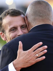 French President Emmanuel Macron, left, is greeted