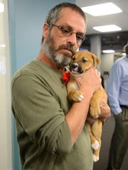 Pensacola News Journal reporter Troy Moon cuddles with a puppy from the Pensacola Humane Society in December 2014 during a tour with the pets to raise awareness for adoption.