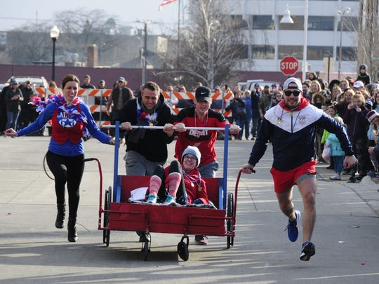 Members of the Young Professionals team run in the bed races at the Port Huron Chilly Fest on Saturday, Jan. 27, 2018.