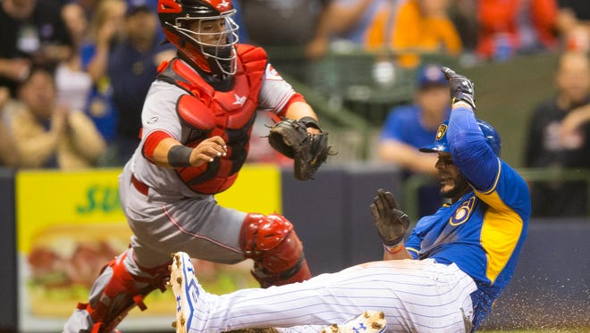 Milwaukee Brewers shortstop Jonathan Villar (5) slides into home as Cincinnati Reds catcher Ramon Cabrera (37) tries to make a diving tag during the fourth inning at Miller Park.