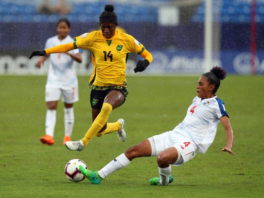 Jamaica midfielder Deneisha Blackwood (14) leaps as Panama midfielder Katherine Castillo (4) kicks the ball away  during the first half of the third place match of the CONCACAF women's World Cup qualifying tournament, Wednesday, Oct. 17, 2018, in Frisco, Texas. (AP Photo/Richard W. Rodriguez)
