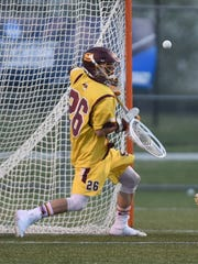 Senior goalie Colin Reymann saves a shot from Cabrini's offense.