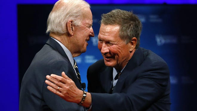 Former Vice President Joe Biden, left, and then-Ohio Gov. John Kasich embrace after discussing the bridging of political and partisan divides at the Biden Institute at the former vice president's alma mater, the University of Delaware, on Oct. 17, 2017.