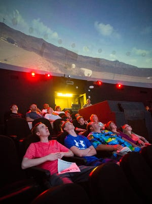 Visitors to the New Horizons Dome Theater & Planetarium at the New Mexico Museum of Space History in Alamogordo look up at the planetarium's curved screen before the start of a show, July 8, 2016.