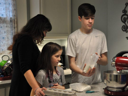 Jen Knights and her daughter Mae, 10, and son Arlo, 13, bake cookies at their Iowa City home on Dec. 17, 2017.