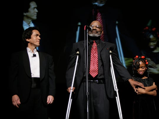 """Anthony (Cass) Castelow, center, with his daughter, Myracle, told his story from homelessness to godliness at the Fox Theatre in 2009, when Mitch Albom, left, held a charity event to launch his book """"Have a Little Faith."""""""