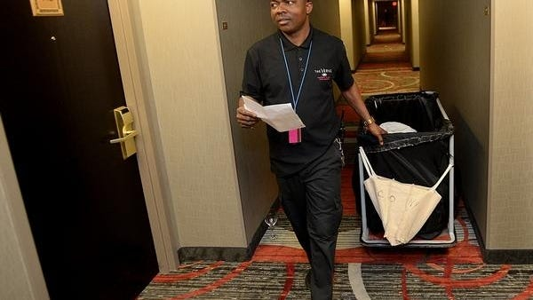 Conic Nyenpan, of Framingham, makes his rounds while at work as a house attendant at a Natick hotel in this 2018 file photo. The leisure and hospitality sector was among the hardest hit during the pandemic this year but last month showed strong gains in hiring.
