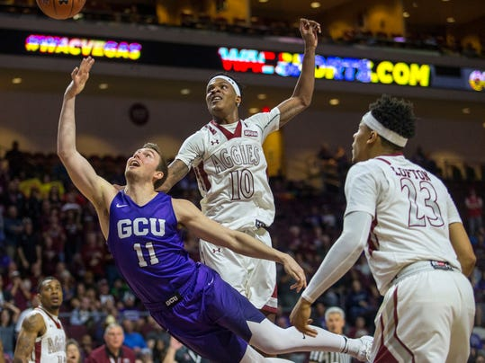 Grand Canyon guard Casey Benson (11) shoots while diving past New Mexico State forward Jemerrio Jones (10) and guard Zach Lofton (23) during the first half of an NCAA college basketball game in the Western Athletic Conference men's tournament final Saturday, March 10, 2018, in Las Vegas. (AP Photo/L.E. Baskow)