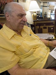 Gregory Melikian, 94, reads off a review of his hotel by the New York Times on May 30, 2018, in downtown Phoenix.