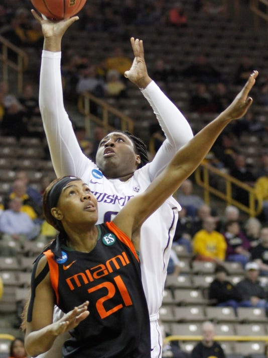 Washington center Chantel Osahor (0) takes a shot from behind Miami guard Brianna Ruiz (21) during the first half of a women's college basketball game in the first round of the NCAA tournament in Iowa City, Iowa, Friday March 20, 2015. (AP Photo/Matthew Holst)