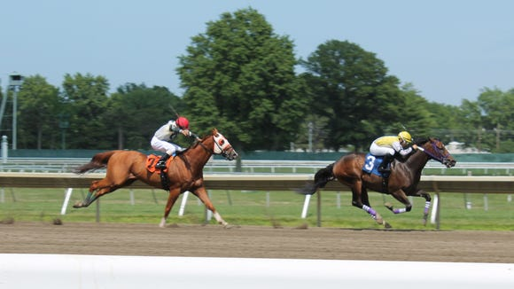 The leading competitors close in on the finish line at Monmouth Park Racetrack