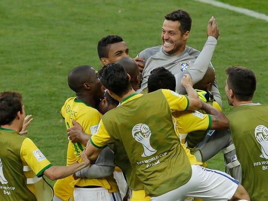 Brazil's goalkeeper Julio Cesar, top, is congratulated by his teammates after the World Cup round of 16 soccer match between Brazil and Chile at the Mineirao Stadium in Belo Horizonte, Brazil, Saturday, June 28, 2014. Brazil won 3-2 on penalties after the match ended 1-1 draw after extra-time. (AP Photo/Hassan Ammar)