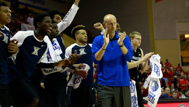 Xavier Musketeers head coach Chris Mack and teammates react and celebrate against the Dayton Flyers during the first half at HP Field House.