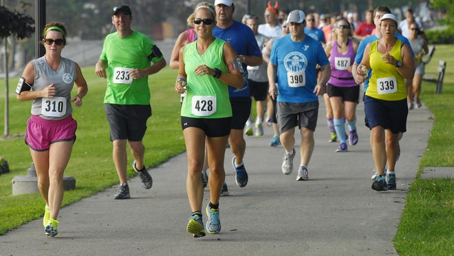 Amy Schock-McNeill, of Fort Gratiot, runs along the race route along Pine Grove Park, Sun, Jun 29, during the Blue Water Half Marathon.