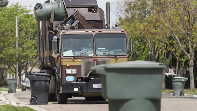 A Visalia City garbage truck picks up green waste on Huntington Street on Tuesday. The city of Visalia is considering a switch to private vendors for refuse pickup.