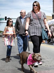 Roxie (the dog) takes her family for a stroll at the