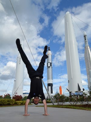 Zach Bosch,  content specialist for Kennedy Space Center Visitor Complex does a handstand amid rockets.