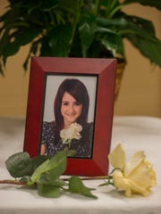 A photo of murder victim Amber Robinson sits on a table Sunday at a memorial at Guy Thompson Community Center in Milton.