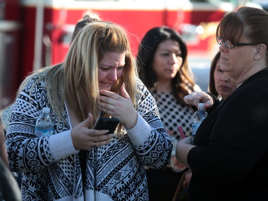 A woman cries at the scene of an active shooting on