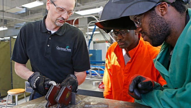 Mike Devore, left, gives welding instructions to Alphonsus Akujobi, center, and El Hassane Kamagaté during a mechanical engineering technology class at Cincinnati State Technical and Community College. Advanced manufacturing skills are in high demand.