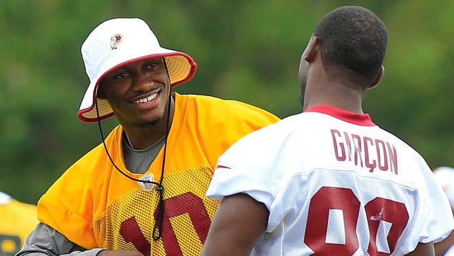 Redskins quarterback Robert Griffin III (10) jokes with wide receiver Pierre Garcon (88).