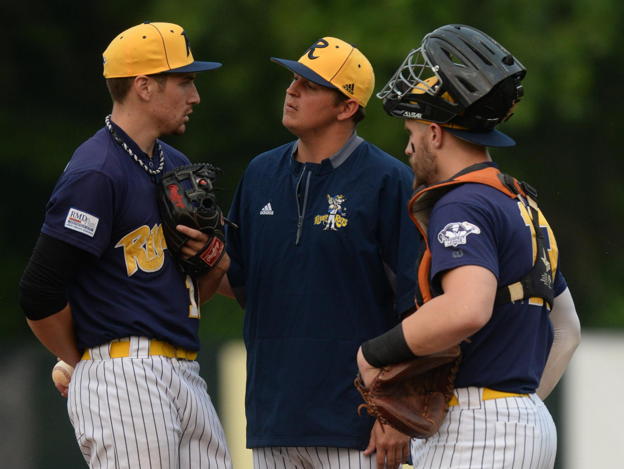 Richmond RiverRat assistant coach Patrick Flanagan talks to pitcher Joe Pourier, left, with catcher Brian Hakes during a game last month. Flanagan was hired recently as Eaton's new varsity baseball coach.