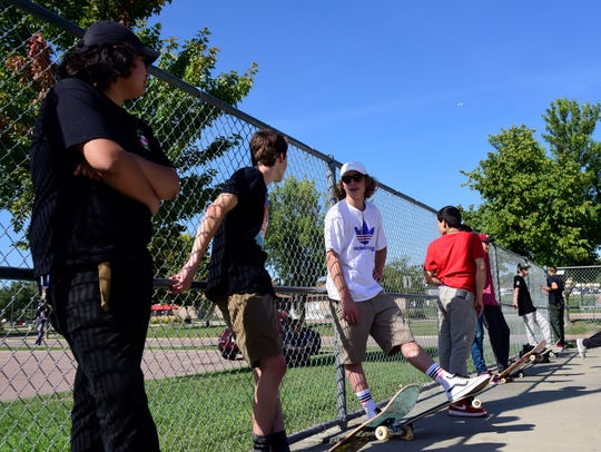 A group of skaters hangs out in the shade of a tree