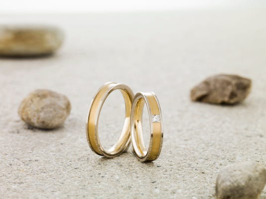 Wedding rings balanced on stone