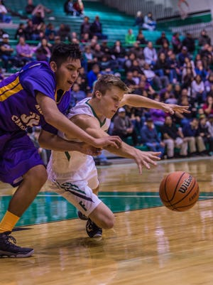 Farmington's Sol Rascon, right, and Kirtland Central's Noah Lee dive for the ball during a game on Tuesday at Scorpion Gym in Farmington.