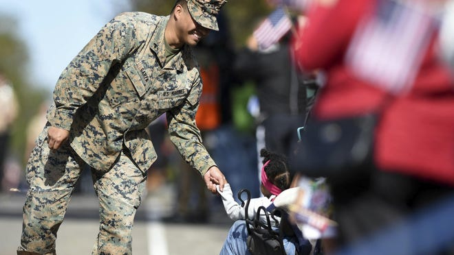 Cpl. Marco Garza with the United States Marine Corp greets spectators along Front St. during the Southeast North Carolina Veterans Day Parade in downtown Wilmington, N.C., Saturday, Nov. 10, 2018. (Matt Born/The Star-News via AP)